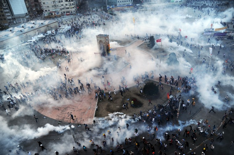 """People run away as Turkish riot policemen fire tear gas on Taksim square on June 11, 2013. Turkish police fired massive volleys of tear gas and jets of water to disperse thousands of anti-government demonstrators in Istanbul's Taksim Square on June 11, after earlier apparently retreating, an AFP reporter saw. The gas sent the crowd scrambling, raising tensions on a 12th day of violence after Prime Minister Recep Tayyip Erdogan warned he had """"no more tolerance"""" for the mass demonstrations. (Bulent Kilic/Getty Images)"""