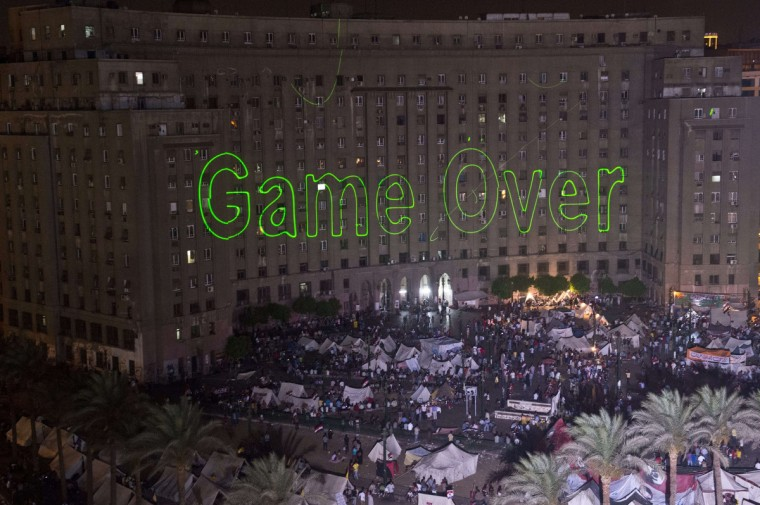 "Egyptian protesters calling for the ouster of President Mohamed Morsi gather in Cairo's landmark Tahrir Square on July 2, 2013 as laser lights (L) directed at the government building spell ""Game Over."" (Khaled Desouki/Getty Images)"