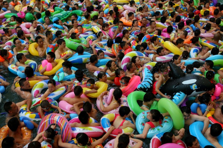 This picture taken on July 27, 2013 shows people trying to cool off at a water park in Suining, southwest China's Sichuan province, as a heatwave hit several provinces in China. Much of China is in the grip of a summer heatwave, and the China Meteorological Association issued a high temperature warning for several eastern and central provinces, saying temperatures could reach 41 degrees Celsius (106 Fahrenheit) on July 31. (Getty Images)