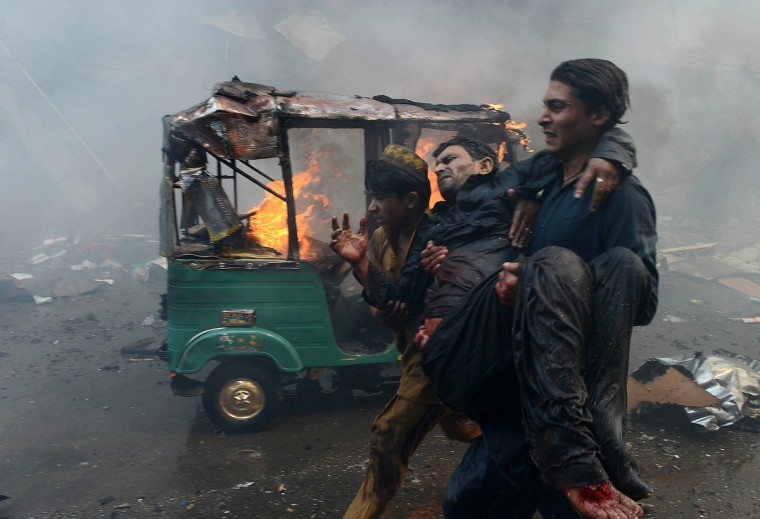 Pakistani men carry an injured blast victim at the site of a bomb explosion in the busy Kissa Khwani market in Peshawar on September 29, 2013. A bomb explosion killed at least 31 people in Pakistan's northwestern city of Peshawar, officials said -- the third deadly strike to hit the city in the last week. (Hasham Ahmed/Getty Images)
