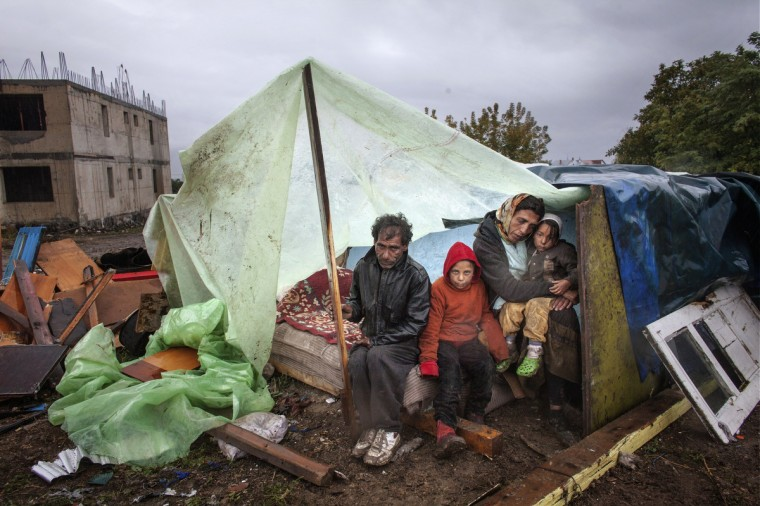 A Roma family of turkish origin sits under an improvised shelter to protect from heavy rain in Eforie Sud, Romania, on September 30, 2013 before an announcement by the Mayor on their case. Romanian authorities evicted around 100 Roma from a town near the Black Sea coast without providing them with alternative housing, prompting criticism from Amnesty International. The Roma families spent three days in a nearby field despite the cold weather until the mayor decided on September 30, 2013 to host them in an old school. (Mugur Varzariu/Getty Images)