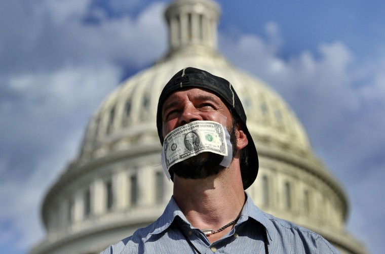 """A protester covers his mouth with a dollar bill as he joins others in a demonstration in front of the US Capitol in Washington, DC, on October 1, 2013 urging congress to pass the budget bill. US President Obama slammed Republicans for shutting down the government as part of an """"ideological crusade"""" designed to kill his signature health care law. The US government shut down on October 1, 2013 for the first time in 17 years after a gridlocked Congress failed to reach a federal budget deal amid bitter brinkmanship. Some 800,000 federal workers have been furloughed in a move reminiscent of two previous shutdowns -- for six days in November 1995 and 21 days from December that year into early 1996. (Jewel Samad/Getty Images)"""