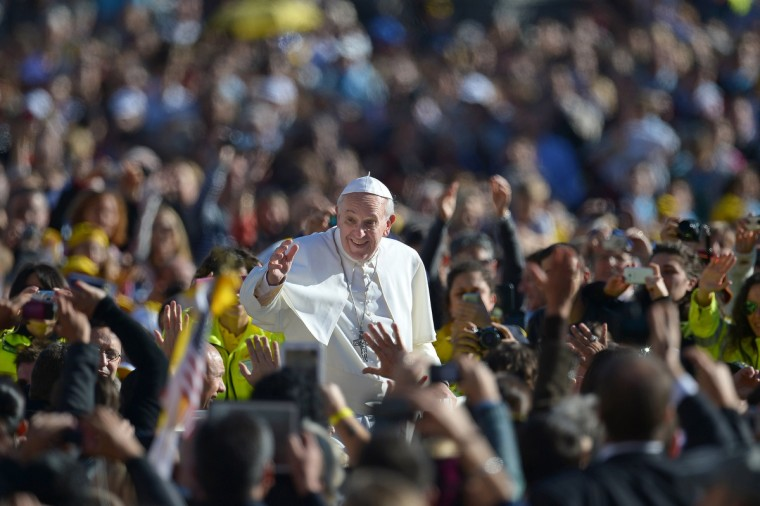 Pope Francis salutes the crowd as he arrives for his general audience in St Peter's square at the Vatican on November 6, 2013. (Vincenzo Pinto/Getty Images)