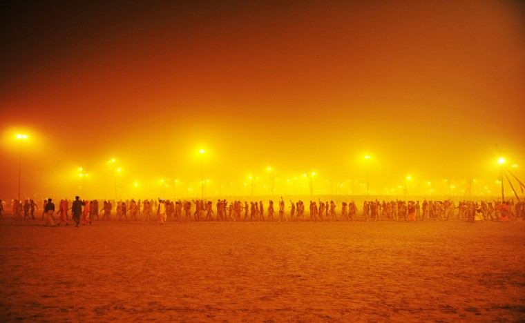 Sadhus or holy men walk in a procession towards the Sangham or the confluence of the the Yamuna and Ganges rivers to bathe before sunrise during the Kumbh Mela in Allahabad on January 14, 2013. Hundreds of thousands of Hindu pilgrims led by naked, ash-covered holy men streamed into the sacred river Ganges on Monday at the start of the world's biggest religious festival. The Kumbh Mela in the Indian town of Allahabad will see up to 100 million worshippers gather over the next 55 days to take a ritual bath in the holy waters, believed to cleanse sins and bestow blessings. Before daybreak on Monday, a day chosen by astrologers as auspicious, hundreds of gurus, some brandishing swords and tridents, ran into the swirling and freezing waters for the first bath, signalling the start of events. (Sanjay Kanojia/Getty Images)