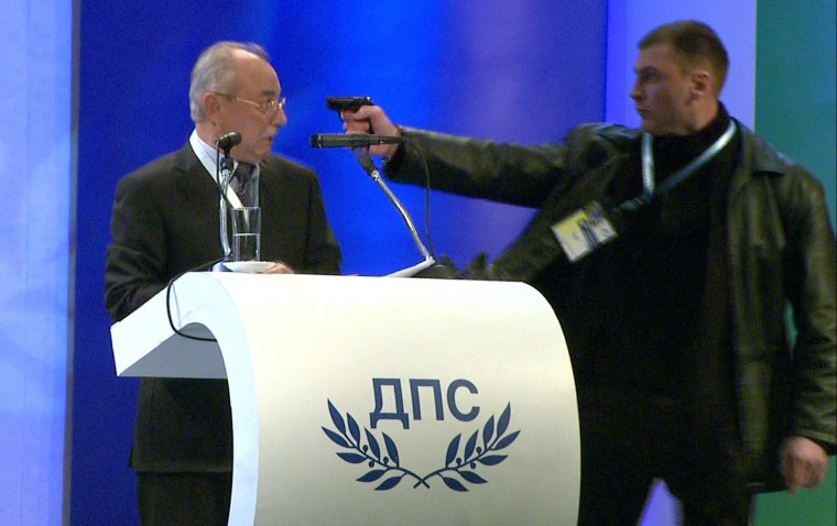 This video grab broadcast by Bulgarian television channel BTV shows a man (R) pointing a pistol at leader of the Turkish minority Movement for Rights and Freedoms (MRF) party Ahmed Dogan during his speech at a national party conference in Sofia on January 19, 2013. Dogan was addressing the delegates at the conference when the man rushed up to the podium and put a pistol to his head. The attacker however failed to produce a shot and was quickly disarmed by the delegates, witnesses told state BNR radio. (Getty Images)