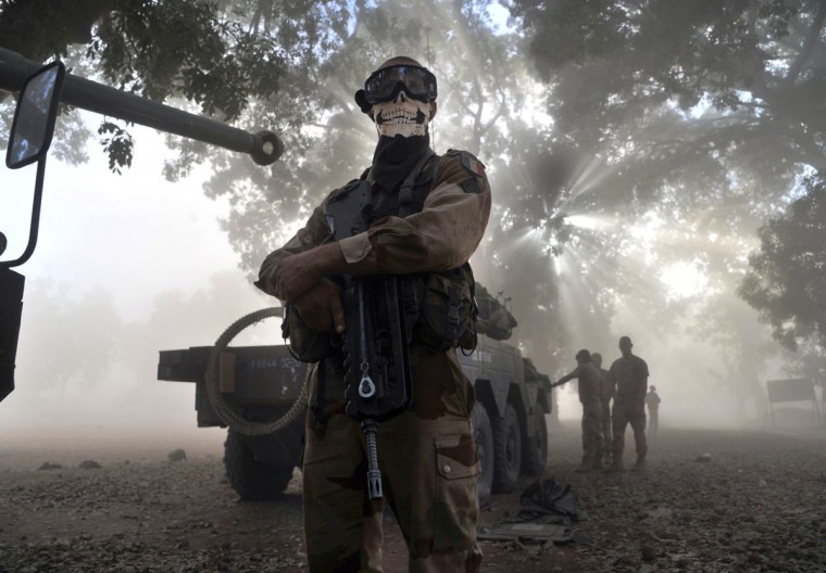 """A soldier of the French foreign legion wearing a skeleton mask stands next to an armored vehicule in a street in Niono, on January 20, 2013. French Defence Minister Jean-Yves Le Drian said today that the goal of France's military action in Mali was to retake control of the entire country from Islamist militants who have seized the north. """"The goal is the total reconquest of Mali. We will not leave any pockets"""" of resistance, Le Drian said on French television. (Issouf Sanogo/Getty Images)"""