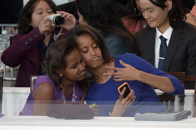 Sasha (L) and Malia Obama, daughters of US President Barack Obama, take a photo of themselves during the Presidential Inaugural Parade on January 21, 2013 in Washington, DC. (Joe Klamar/Getty Images)