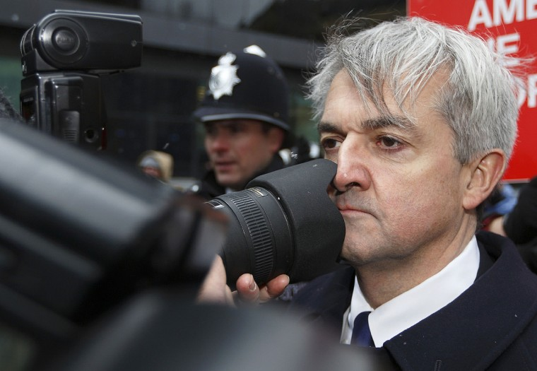 Former British energy minister Chris Huhne (R) comes into contact with a photographers lens as he arrives at Southwark Crown Court in London, on March 11, 2013. Huhne and his ex-wife Vicky Pryce are due to be sentenced later Monday for perverting the course of justice over speeding points a decade ago. (Justin Tallis/Getty Images)