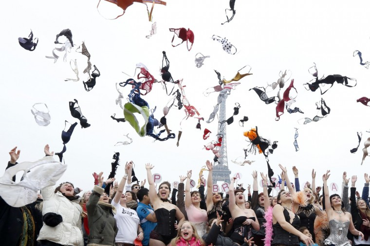 "Woman throws bras on March 25, 2013 at the esplanade des droits de l'homme, in front of the Eiffel tower in Paris, during a happening called by ""Pink Bra Bazzar, a French organization fighting against and sensitizing on breast cancer. (Pierre Verdy/Getty Images)"
