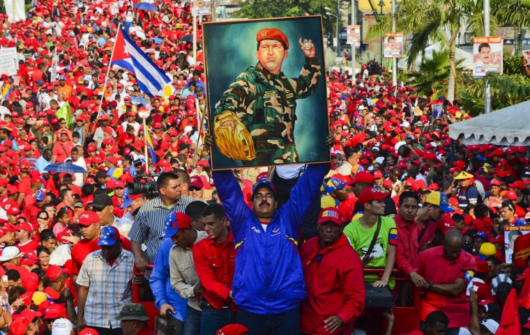 Venezuela's acting President Nicolas Maduro holds a picture of the late president Hugo Chavez during a campaign rally in Catia la mar, state of Vargas on April 9, 2013. Venezuelans will elect new president next April 14 and the final stretch of Venezuela's race to replace Hugo Chavez coincides with a delicate anniversary for the opposition: 11 years since a brief coup against the late leftist leader. (Luis Acosta/Getty Images)