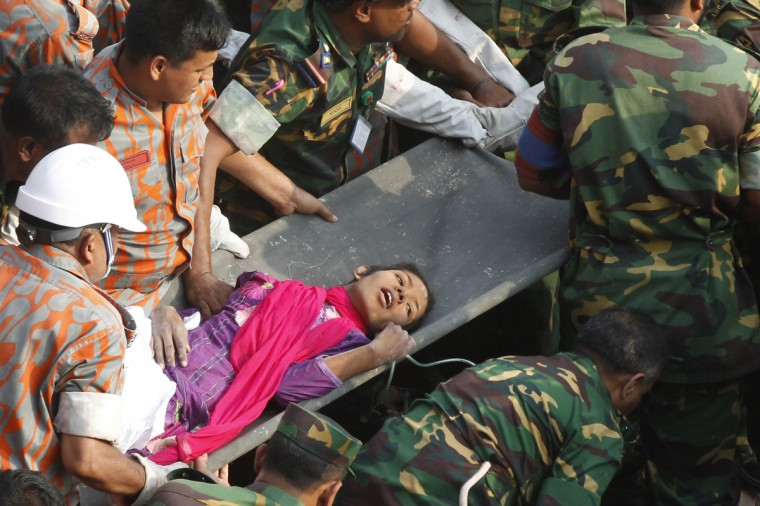 Bangladeshi rescuers retrieve garment worker Reshma from the rubble of a collapsed building in Savar on May 10, 2013, seventeen days after the eight-story building collapsed. The death toll from last month's collapse of a garment factory complex in Bangladesh rose past 1,000 as piles of bodies were found in the ruins of a stairwell where victims had sought shelter. (Getty Images)