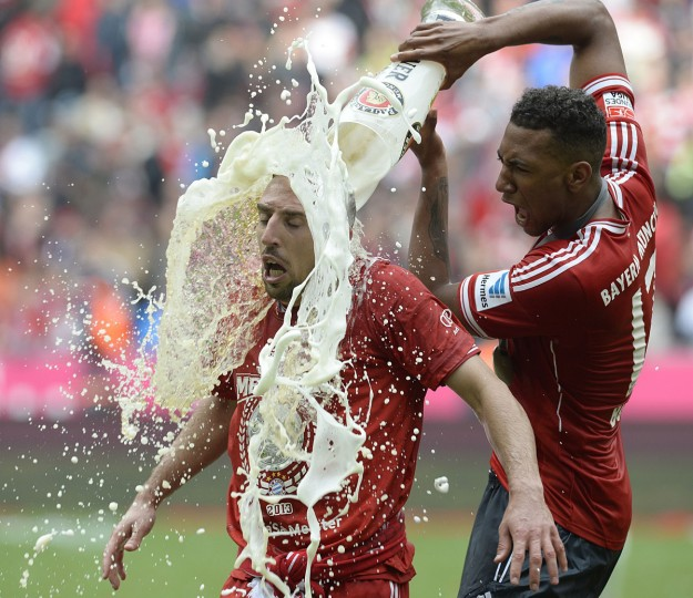 Bayern Munich's defender Jerome Boateng (R) pours beer on Bayern Munich's French midfielder Franck Ribery while celebrating their champion title, after winning 3:0 the German first division Bundesliga football match between Bayern Munich and FC Augsburg in Munich, southern Germany, on May 11, 2013. Munich were confirmed German league champions back on April 6, when they won the Bundesliga with a record six games left to play. (Christof Stache/Getty Images)