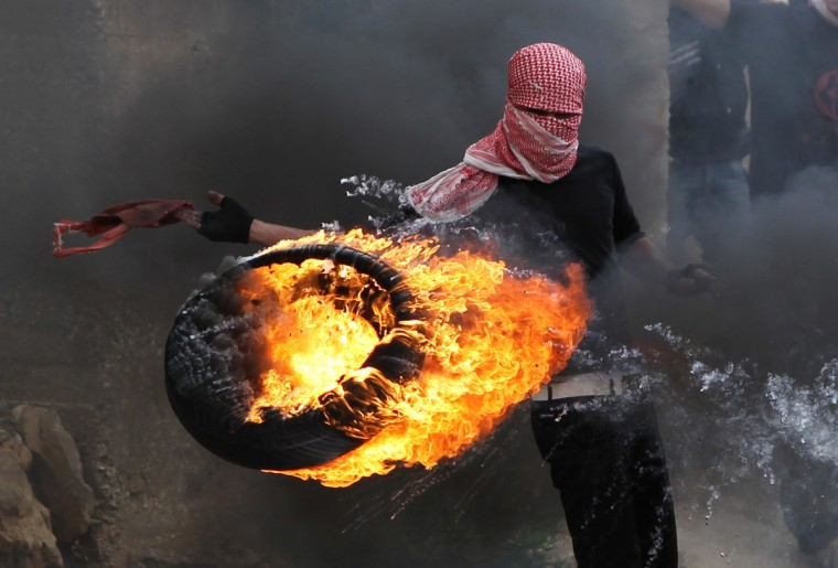 """A Palestinian sets fire to a tyre during clashes between hundreds of Palestinians and Israeli soldiers outside the Ofer prison after a march marking the 65th Nakba day or """"Day of Catastrophe"""" on May 15, 2013 in Betunia near the West Bank city of Ramallah. (Abbas Momani/Getty Images)"""