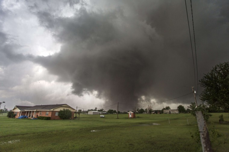 This photo shows the approaching tornado on May 20, 2013 in Moore, Oklahoma. Families returned to a blasted moonscape that had been an American suburb May 21, 2013 after the monstrous tornado tore through the outskirts of Oklahoma City, killing at least 24 people. Nine children were among the dead and entire neighborhoods vanished, with often the foundations being the only thing left of what used to be houses and cars tossed like toys and heaped in big piles. (Vincent Deligny/Getty Images)