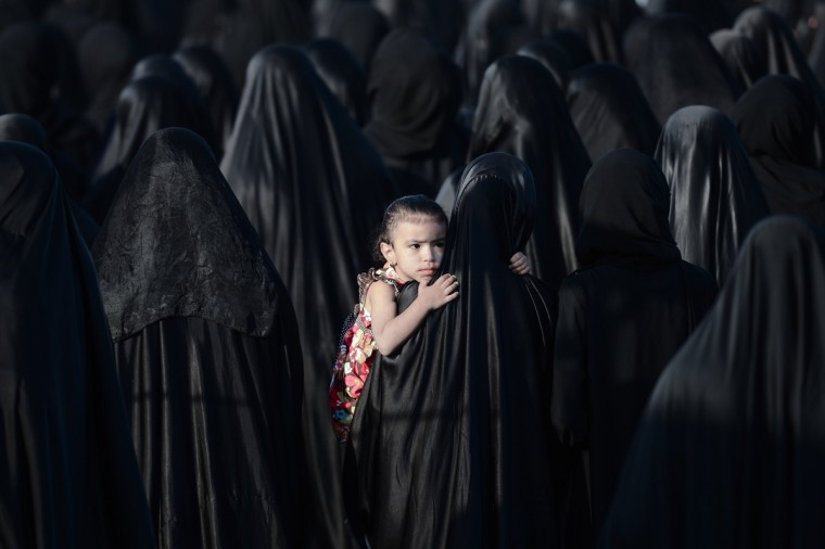 A Bahraini girl is carried by her mother during the funeral of Sayed Omran Sayed Hameed, on May 28, 2013, in the village of Karzakkan, south of Manama. Hameed, 26, died at hospital after developing respiratory complications and his relatives claim that his death is due to the inhalation of poisonous tear gas that riot police used during a protest in May 2013. (Mohammed Al-Shaikh/Getty Images)