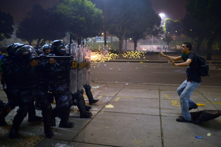 A demonstrator is shot by rubber bullets as anti riot police officers charge after clashes erupted during a protest against corruption and price hikes, on June 20, 2013, in Rio de Janeiro. Brazilians took to the streets again Thursday in several cities on a new day of mass nationwide protests, demanding better public services and bemoaning massive spending to stage the World Cup. (Christofe Simon/Getty Images)