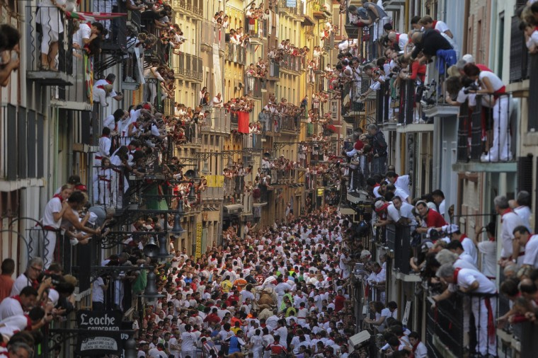 People standing on balconies look at participants as they run in front of Alcurrucen's bulls during the first bull run of the San Fermin Festival, on July 7, 2013, in Pamplona, northern Spain. The festival is a symbol of Spanish culture that attracts thousands of tourists to watch the bull runs despite heavy condemnation from animal rights groups. (Pedro Armestre/Getty Images)
