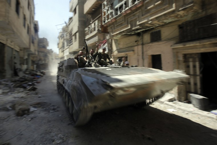Soldiers of the Syrian government forces patrol on a tank in a devastated street on July 31, 2013 in the district of al-Khalidiyah in the central Syrian city of Homs. The Syrian government announced the capture of Khalidiyah, a key rebel district in Homs, Syria's third city and a symbol of the revolt against President Bashar al-Assad. (Joseph Eid/Getty Images)