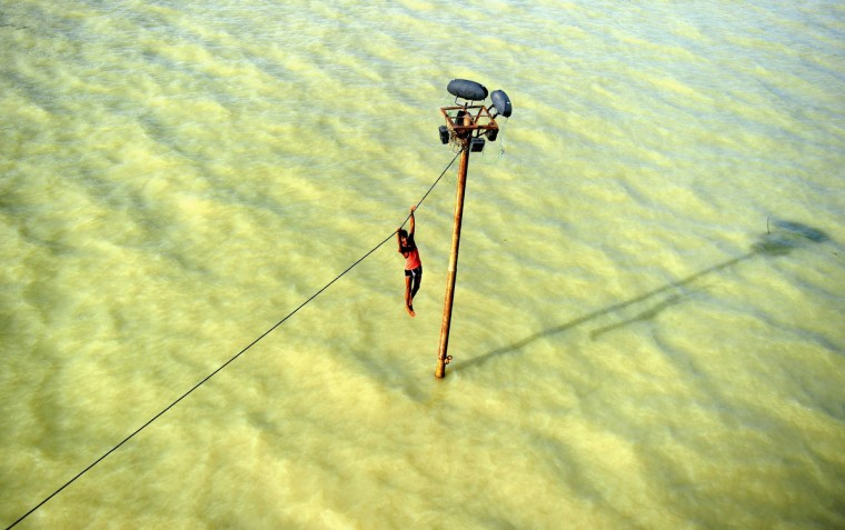 An Indian youth dangles from a power line before diving into the floodwaters of an overflowing Ganges river in Allahabad on August 6, 2013. The monsoon, which covers the subcontinent from June to September and usually brings flooding, accounts for about 80 percent of India's annual rainfall. (Sanjay Kanojia/Getty Images)