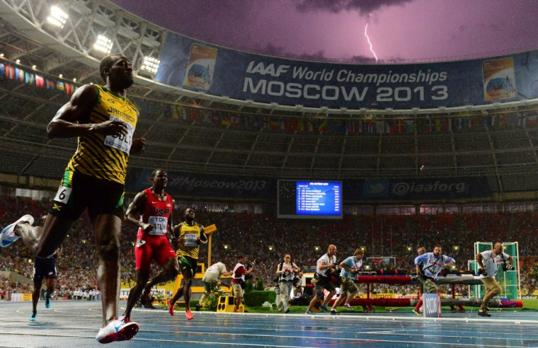 Jamaica's Usain Bolt (L) wins the100 metres final at the 2013 IAAF World Championships at the Luzhniki stadium in Moscow on August 11, 2013 while a lightning strikes in the sky. Bolt timed a season's best 9.77 seconds, with American Justin Gatlin claiming silver in 9.85sec and Nesta Carter, also of Jamaica, taking bronze in 9.95sec. (Olivier Morin/Getty Images)