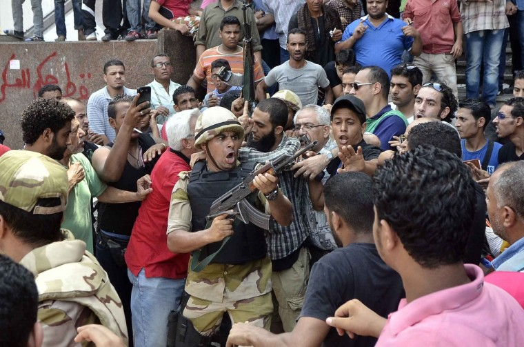 An army officer tries to control the crowd as he escorts an Islamist man out of Cairo's Al-Fath mosque where Islamist supporters of ousted president Mohamed Morsi held up on August 17, 2013. The standoff at al-Fath mosque in central Ramses Square began on August 16, with security forces surrounding the building where Islamists were sheltering and trying to convince them to leave. (Mohamed El-Shahed/Getty Images)