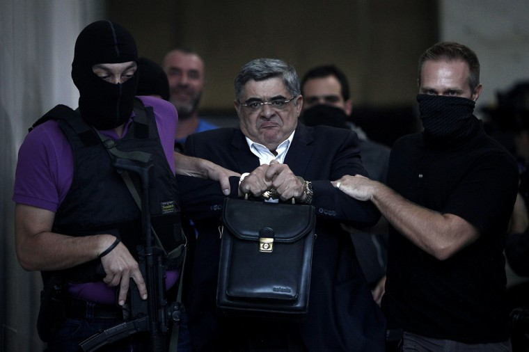 The leader of ultra-right wing Golden Dawn party Nikos Michaloliakos is escorted by masked police officers to the prosecutor from the police headquarters in Athens on September 28, 2013. Greek police on Saturday swooped on the neo-Nazi Golden Dawn party, arresting its leadership and hunting for dozens of members across the country in a crackdown sparked by the murder of a leftist musician. The arrests came a day after Golden Dawn threatened to pull its lawmakers out of parliament, a move that could spark a political crisis in the recession-hit country. (Angelos Tzortzinis/Getty Images)