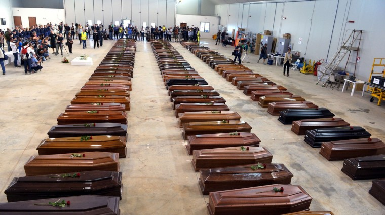 Coffin of victims are seen in an hangar of Lampedusa airport on October 5, 2013 after a boat with migrants sank killing more than hundred people. Italy mourned today the 300 African asylum-seekers feared dead in the worst ever Mediterranean refugee disaster, as the government appealed for Europe to stem the influx of migrants. Italian emergency services hoped to resume the search for bodies on October 5, 2013 despite rough seas after the accident, in which 111 African asylum-seekers are confirmed dead and around 200 more are still missing. (Alberto Pizzoli/Getty Images)