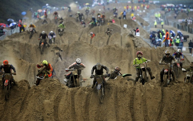 Riders reach the crest of a dune during the opening lap of the main race of the 2013 RHL Weston beach race in Weston-Super-Mare, southwest England, on October 13, 2013. Beach racing is an offshoot of enduro and motocross racing. Riders on solo motorcycles and quad bikes compete on a course marked out on a beach, with man-made jumps and sand dunes being constructed to make the course tougher. Riders race along the beach and across a series of sand dunes in a three-hour endurance race. (Adrian Dennis/Getty Images)