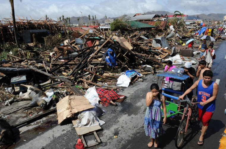 Residents walk past destroyed houses and dead bodies littered along a road in Tacloban, on the eastern island of Leyte on November 10, 2013 after Super Typhoon Haiyan swept over the Philippines. The typhoon that destroyed entire towns across the Philippines is believed to have killed more than 10,000 people, authorities said on November 10, which would make it the country's deadliest recorded natural disaster. (Ted Aljibe/Getty Images)