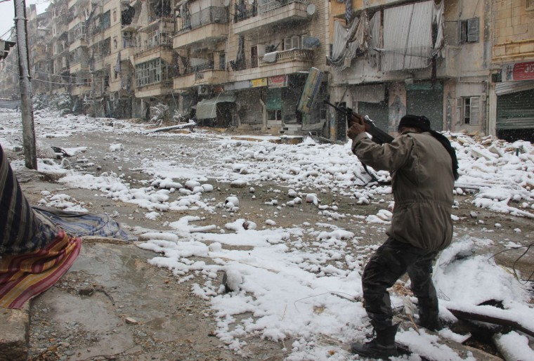 """A rebel fighter aims his weapon as he stands amidst snow during clashes with Syrian pro-government forces in the Salaheddin neighbourhood of Syria's northern city of Aleppo. Gulf Arab states called for the withdrawal of """"all foreign forces"""" from Syria, where Iran-backed Shiite militias from Iraq and Lebanon are supporting regime troops against mostly-Sunni rebels. (Medo Halb/Getty Images)"""