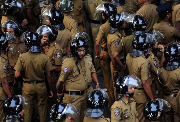 Sri Lankan police block a road leading to President Mahinda Rajapakses office during a demonstration held by the opposition Peoples Liberation Front party (JVP) in Colombo. The JVP is protesting high living costs and demanding higher government spending on education. (Ishara S.Kodikasra/Getty Images)