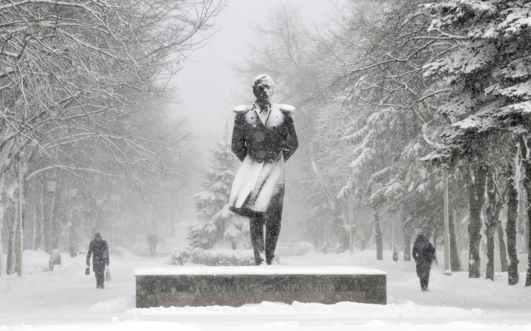 People walk past a monument to Russian poet Mikhail Lermontov during a major snowfall in the southern Russian city of Stavropol, on December 11, 2013. Snow fell today across Stavropol, while temperatures dropped to -10 C (14 F), but due to high humidity and wind, weather experts said it would feel more like - 18 C (-1 F). (Danil Semyonov/Getty Images)