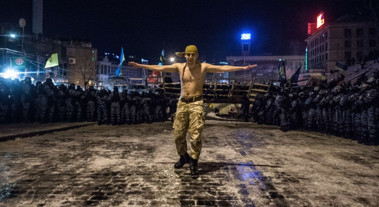 """A protester stands next to riot policemen getting ready to launch an assault to a barricade held by protesters on Independence Square in Kiev late on December 11, 2013. Ukrainian security forces on Wednesday stormed Kiev's Independence Square which protesters have occupied for over a week but the demonstrators defiantly refused to leave and resisted the police in a tense standoff. Eite Berkut anti-riot police and interior ministry special forces moved against the protestors at around 2:00 am (midnight GMT) in a move that prompted US Secretary of State John Kerry to express """"disgust"""" over the crackdown. (Dmitry Serebryakov/Getty Images)"""