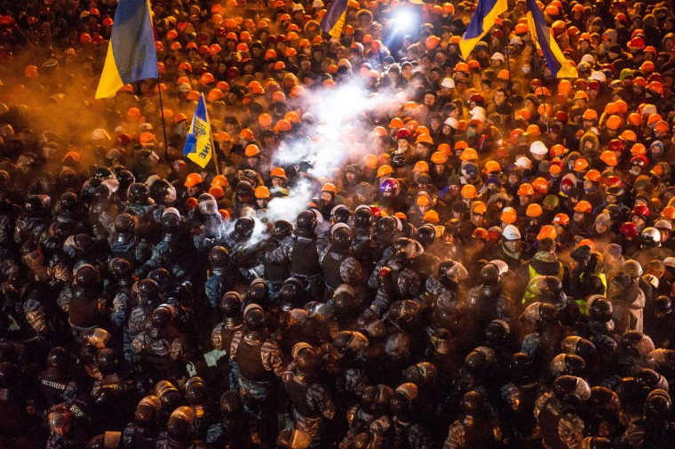"""Riot police clash with pro-EU protesors on Independence Square in Kiev early on December 11,2013. Ukrainian security forces stormed Kiev's Independence Square which protesters have occupied for over a week but the demonstrators defiantly refused to leave and resisted the police in a tense standoff. Eite Berkut anti-riot police and interior ministry special forces moved against the protestors at around 2:00 am (midnight GMT) in a move that prompted US Secretary of State John Kerry to express """"disgust"""" over the crackdown. (Volodymyr Shuvayev/Getty Images)"""