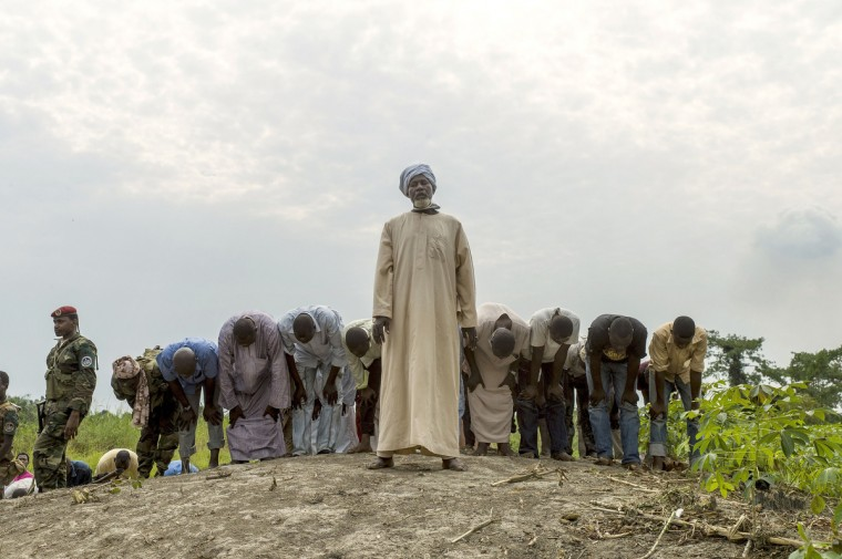 People pray as they bury 16 coffins in the muslim cemetery of the PK16 district of Bangui. The father of a slain French soldier has described how disarmed Muslim fighters in the Central African Republic were lynched by a Christian mob in harrowing testimony that raised the spectre of a new wave of sectarian killing in the troubled state. (Fred Dufour/Getty Images)