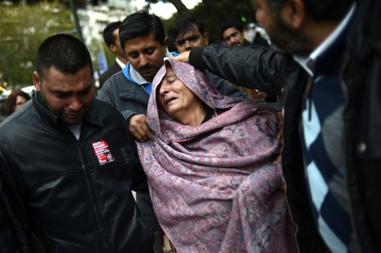 The mother of a 27-year-old Pakistani man stabbed to death reacts as she leaves an Athens court where two suspected members of the Greek neo-Nazi party Golden Dawn accused of her son's murder are being judged on December 18, 2013. The case is coming to trial three months after the fatal stabbing of a leftist rapper by a Golden Dawn supporter, which paved the way for a crackdown on the neo-Nazi group with six of its members charged with belonging to a criminal group. Dionyssis Liakopoulos, 25, and Christos Steriopoulos, 29, risk a life sentence if found guilty of the drive-by killing of Shehzad Luqman in Athens last January. (Aris Messinis/Getty Images)
