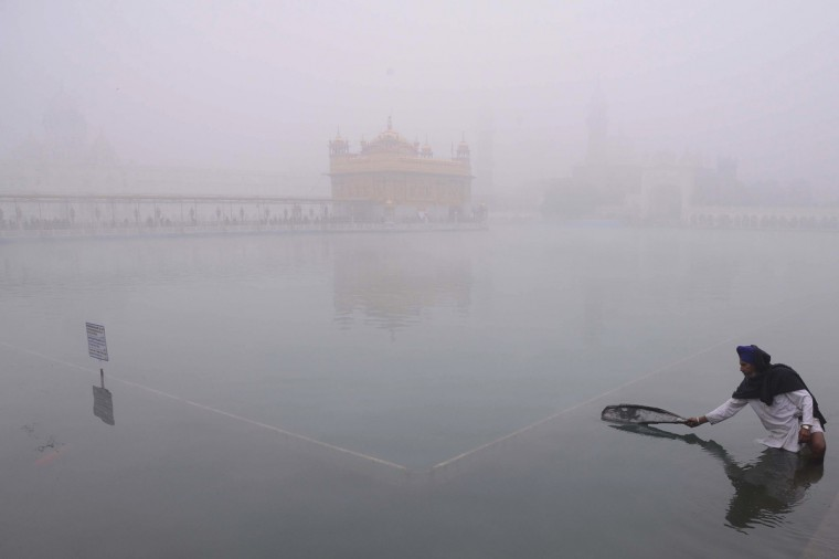 An Indian Sikh devotee cleans the sarover (water pool) at a fog-shrouded Golden Temple in Amritsar. Seasonal heavy fog and cold weather disturbed train, bus and air schedules in northern India as temperatures dipped towards freezing. (Narinder Nanu/Getty Images)