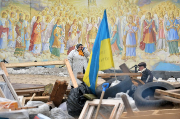 """Opposition activists guard a barricade in front of a fresco of Mykhaylo Gold Dome cathedral in Kiev. Ukraine's prime minister on Wednesday defended a deal with the Kremlin that the opposition decried as a sellout to Russia, saying that Kiev had avoided bankruptcy and social collapse thanks to the """"historic"""" bailout. Prime Minister Mykola Azarov said the agreement clinched between President Viktor Yanukovych and his Russian counterpart Vladimir Putin on Tuesday was the only way to rescue the economy after five consecutive quarters of negative growth. (Sergei Supinsky/Getty Images)"""