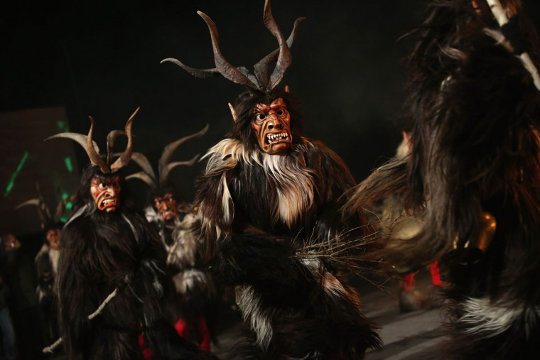 Members of the Haiminger Krampusgruppe dressed as the Krampus creature parade on the town square during their annual Krampus night in Tyrol on December 1, 2013 in Haiming, Austria. Krampus, in Tyrol also called Tuifl, is a demon-like creature represented by a fearsome, hand-carved wooden mask with animal horns, a suit made from sheep or goat skin and large cow bells attached to the waist that the wearer rings by running or shaking his hips up and down. Krampus has been a part of Central European, alpine folklore going back at least a millennium, and since the 17th-century Krampus traditionally accompanies St. Nicholas and angels on the evening of December 5 to visit households to reward children that have been good while reprimanding those who have not. However, in the last few decades Tyrol in particular has seen the founding of numerous village Krampus associations with up to 100 members each and who parade without St. Nicholas at Krampus events throughout November and early December. (Sean Gallup/Getty Images)