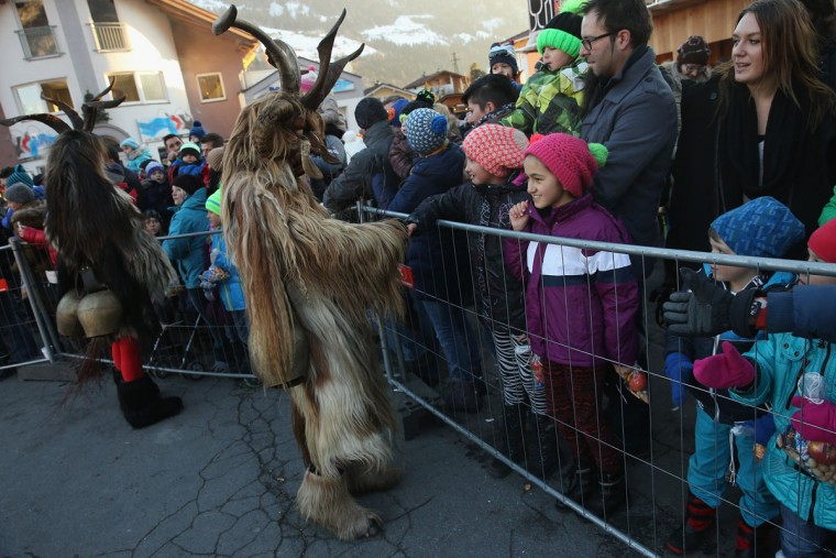 Members of the Haiminger Krampusgruppe dressed as the Krampus creature approach onlookers prior to the annual Krampus night in Tyrol on December 1, 2013 in Haiming, Austria. Krampus, in Tyrol also called Tuifl, is a demon-like creature represented by a fearsome, hand-carved wooden mask with animal horns, a suit made from sheep or goat skin and large cow bells attached to the waist that the wearer rings by running or shaking his hips up and down. Krampus has been a part of Central European, alpine folklore going back at least a millennium, and since the 17th-century Krampus traditionally accompanies St. Nicholas and angels on the evening of December 5 to visit households to reward children that have been good while reprimanding those who have not. However, in the last few decades Tyrol in particular has seen the founding of numerous village Krampus associations with up to 100 members each and who parade without St. Nicholas at Krampus events throughout November and early December. (Sean Gallup/Getty Images)