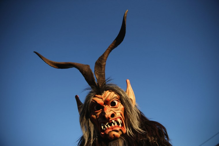 A member of the Haiminger Krampusgruppe dressed as the Krampus creature arrives prior to the annual Krampus night in Tyrol on December 1, 2013 in Haiming, Austria. Krampus, in Tyrol also called Tuifl, is a demon-like creature represented by a fearsome, hand-carved wooden mask with animal horns, a suit made from sheep or goat skin and large cow bells attached to the waist that the wearer rings by running or shaking his hips up and down. Krampus has been a part of Central European, alpine folklore going back at least a millennium, and since the 17th-century Krampus traditionally accompanies St. Nicholas and angels on the evening of December 5 to visit households to reward children that have been good while reprimanding those who have not. However, in the last few decades Tyrol in particular has seen the founding of numerous village Krampus associations with up to 100 members each and who parade without St. Nicholas at Krampus events throughout November and early December. (Sean Gallup/Getty Images)