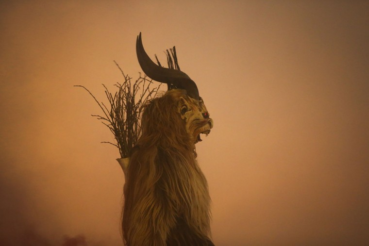 A participant dressed as the Krampus creature walks the streets in search of delinquent children during Krampus night on November 30, 2013 in Neustift im Stubaital, Austria. Sixteen Krampus groups including over 200 Krampuses participated in the first annual Neustift event. Krampus, in Tyrol also called Tuifl, is a demon-like creature represented by a fearsome, hand-carved wooden mask with animal horns, a suit made from sheep or goat skin and large cow bells attached to the waist that the wearer rings by running or shaking his hips up and down. Krampus has been a part of Central European, alpine folklore going back at least a millennium, and since the 17th-century Krampus traditionally accompanies St. Nicholas and angels on the evening of December 5 to visit households to reward children that have been good while reprimanding those who have not. However, in the last few decades Tyrol in particular has seen the founding of numerous village Krampus associations with up to 100 members each and who parade without St. Nicholas at Krampus events throughout November and early December. (Sean Gallup/Getty Images)