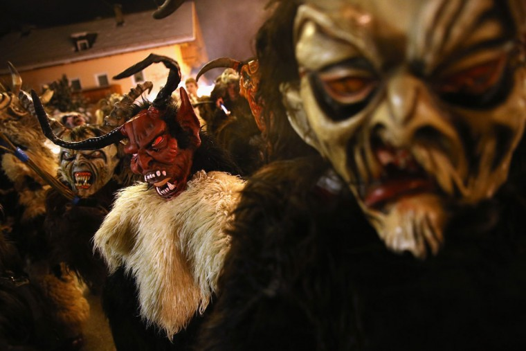 Young children dressed as the Krampus creature wait to parade during Krampus night on November 30, 2013 in Neustift im Stubaital, Austria. Sixteen Krampus groups including over 200 Krampuses participated in the first annual Neustift event. Krampus, in Tyrol also called Tuifl, is a demon-like creature represented by a fearsome, hand-carved wooden mask with animal horns, a suit made from sheep or goat skin and large cow bells attached to the waist that the wearer rings by running or shaking his hips up and down. Krampus has been a part of Central European, alpine folklore going back at least a millennium, and since the 17th-century Krampus traditionally accompanies St. Nicholas and angels on the evening of December 5 to visit households to reward children that have been good while reprimanding those who have not. However, in the last few decades Tyrol in particular has seen the founding of numerous village Krampus associations with up to 100 members each and who parade without St. Nicholas at Krampus events throughout November and early December. (Sean Gallup/Getty Images)