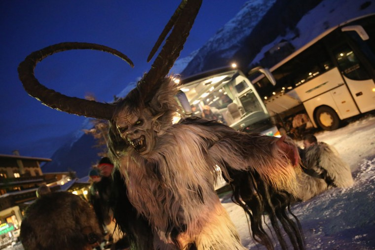 A participant who arrived by bus tries on his Krampus creature mask as other participants put on their costumes prior to Krampus night on November 30, 2013 in Neustift im Stubaital, Austria. Sixteen Krampus groups including over 200 Krampuses participated in the first annual Neustift event. Krampus, in Tyrol also called Tuifl, is a demon-like creature represented by a fearsome, hand-carved wooden mask with animal horns, a suit made from sheep or goat skin and large cow bells attached to the waist that the wearer rings by running or shaking his hips up and down. Krampus has been a part of Central European, alpine folklore going back at least a millennium, and since the 17th-century Krampus traditionally accompanies St. Nicholas and angels on the evening of December 5 to visit households to reward children that have been good while reprimanding those who have not. However, in the last few decades Tyrol in particular has seen the founding of numerous village Krampus associations with up to 100 members each and who parade without St. Nicholas at Krampus events throughout November and early December. (Sean Gallup/Getty Images)