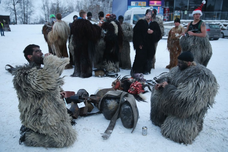 Participants who arrived by bus gather before dressing as the Krampus creature prior to Krampus night on November 30, 2013 in Neustift im Stubaital, Austria. Sixteen Krampus groups including over 200 Krampuses participated in the first annual Neustift event. Krampus, in Tyrol also called Tuifl, is a demon-like creature represented by a fearsome, hand-carved wooden mask with animal horns, a suit made from sheep or goat skin and large cow bells attached to the waist that the wearer rings by running or shaking his hips up and down. Krampus has been a part of Central European, alpine folklore going back at least a millennium, and since the 17th-century Krampus traditionally accompanies St. Nicholas and angels on the evening of December 5 to visit households to reward children that have been good while reprimanding those who have not. However, in the last few decades Tyrol in particular has seen the founding of numerous village Krampus associations with up to 100 members each and who parade without St. Nicholas at Krampus events throughout November and early December. (Sean Gallup/Getty Images)