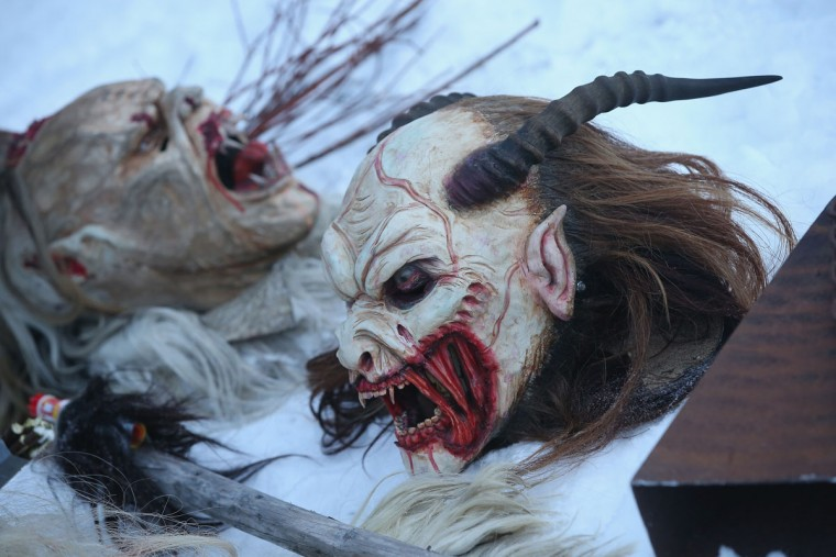 Hand-crafted Krampus masks lie in the snow as participants dress as the Krampus creature prior to Krampus night on November 30, 2013 in Neustift im Stubaital, Austria. Sixteen Krampus groups including over 200 Krampuses participated in the first annual Neustift event. Krampus, in Tyrol also called Tuifl, is a demon-like creature represented by a fearsome, hand-carved wooden mask with animal horns, a suit made from sheep or goat skin and large cow bells attached to the waist that the wearer rings by running or shaking his hips up and down. Krampus has been a part of Central European, alpine folklore going back at least a millennium, and since the 17th-century Krampus traditionally accompanies St. Nicholas and angels on the evening of December 5 to visit households to reward children that have been good while reprimanding those who have not. However, in the last few decades Tyrol in particular has seen the founding of numerous village Krampus associations with up to 100 members each and who parade without St. Nicholas at Krampus events throughout November and early December. (Sean Gallup/Getty Images)