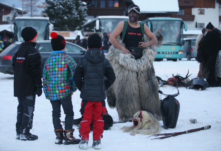 A participant who had arrived by bus chats with children while dressing as the Krampus creature prior to Krampus night on November 30, 2013 in Neustift im Stubaital, Austria. Sixteen Krampus groups including over 200 Krampuses participated in the first annual Neustift event. Krampus, in Tyrol also called Tuifl, is a demon-like creature represented by a fearsome, hand-carved wooden mask with animal horns, a suit made from sheep or goat skin and large cow bells attached to the waist that the wearer rings by running or shaking his hips up and down. Krampus has been a part of Central European, alpine folklore going back at least a millennium, and since the 17th-century Krampus traditionally accompanies St. Nicholas and angels on the evening of December 5 to visit households to reward children that have been good while reprimanding those who have not. However, in the last few decades Tyrol in particular has seen the founding of numerous village Krampus associations with up to 100 members each and who parade without St. Nicholas at Krampus events throughout November and early December. (Sean Gallup/Getty Images)