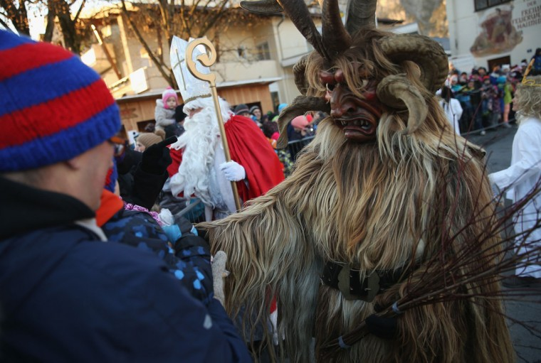 A member of the Haiminger Krampusgruppe dressed as the Krampus creature accompanies St. Nicholas and angels distributing sweets to children prior to the annual Krampus night in Tyrol on December 1, 2013 in Haiming, Austria. Krampus, in Tyrol also called Tuifl, is a demon-like creature represented by a fearsome, hand-carved wooden mask with animal horns, a suit made from sheep or goat skin and large cow bells attached to the waist that the wearer rings by running or shaking his hips up and down. Krampus has been a part of Central European, alpine folklore going back at least a millennium, and since the 17th-century Krampus traditionally accompanies St. Nicholas and angels on the evening of December 5 to visit households to reward children that have been good while reprimanding those who have not. However, in the last few decades Tyrol in particular has seen the founding of numerous village Krampus associations with up to 100 members each and who parade without St. Nicholas at Krampus events throughout November and early December. (Sean Gallup/Getty Images)