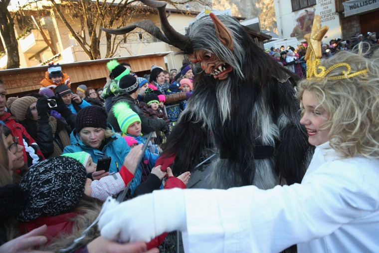A member of the Haiminger Krampusgruppe dressed as the Krampus creature accompanies little girls dressed as angels distributing sweets to children prior to the annual Krampus night in Tyrol on December 1, 2013 in Haiming, Austria. Krampus, in Tyrol also called Tuifl, is a demon-like creature represented by a fearsome, hand-carved wooden mask with animal horns, a suit made from sheep or goat skin and large cow bells attached to the waist that the wearer rings by running or shaking his hips up and down. Krampus has been a part of Central European, alpine folklore going back at least a millennium, and since the 17th-century Krampus traditionally accompanies St. Nicholas and angels on the evening of December 5 to visit households to reward children that have been good while reprimanding those who have not. However, in the last few decades Tyrol in particular has seen the founding of numerous village Krampus associations with up to 100 members each and who parade without St. Nicholas at Krampus events throughout November and early December. (Sean Gallup/Getty Images)