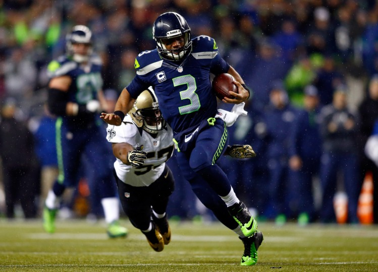 Quarterback Russell Wilson #3 of the Seattle Seahawks runs with the ball as outside linebacker David Hawthorne #57 of the New Orleans Saints defends during a game at CenturyLink Field on December 2, 2013 in Seattle, Washington. (Jonathan Ferrey/Getty Images)